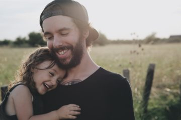 smiling dad holding smiling daughter while standing in a field