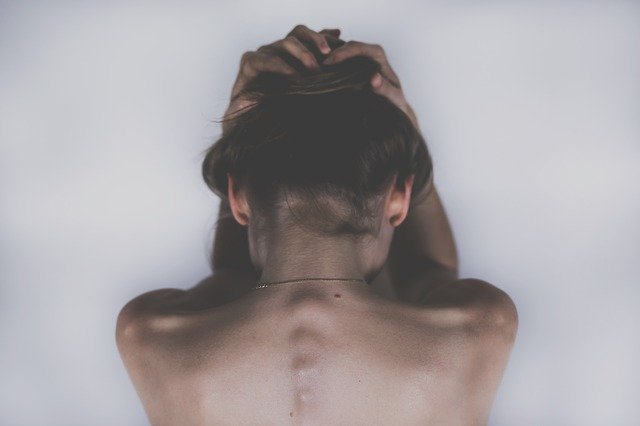 woman with back turned from camera holding her head