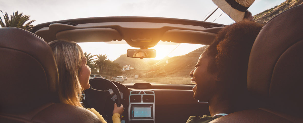 Two girls happily driving their new car because they knew how to save money on a car loan.